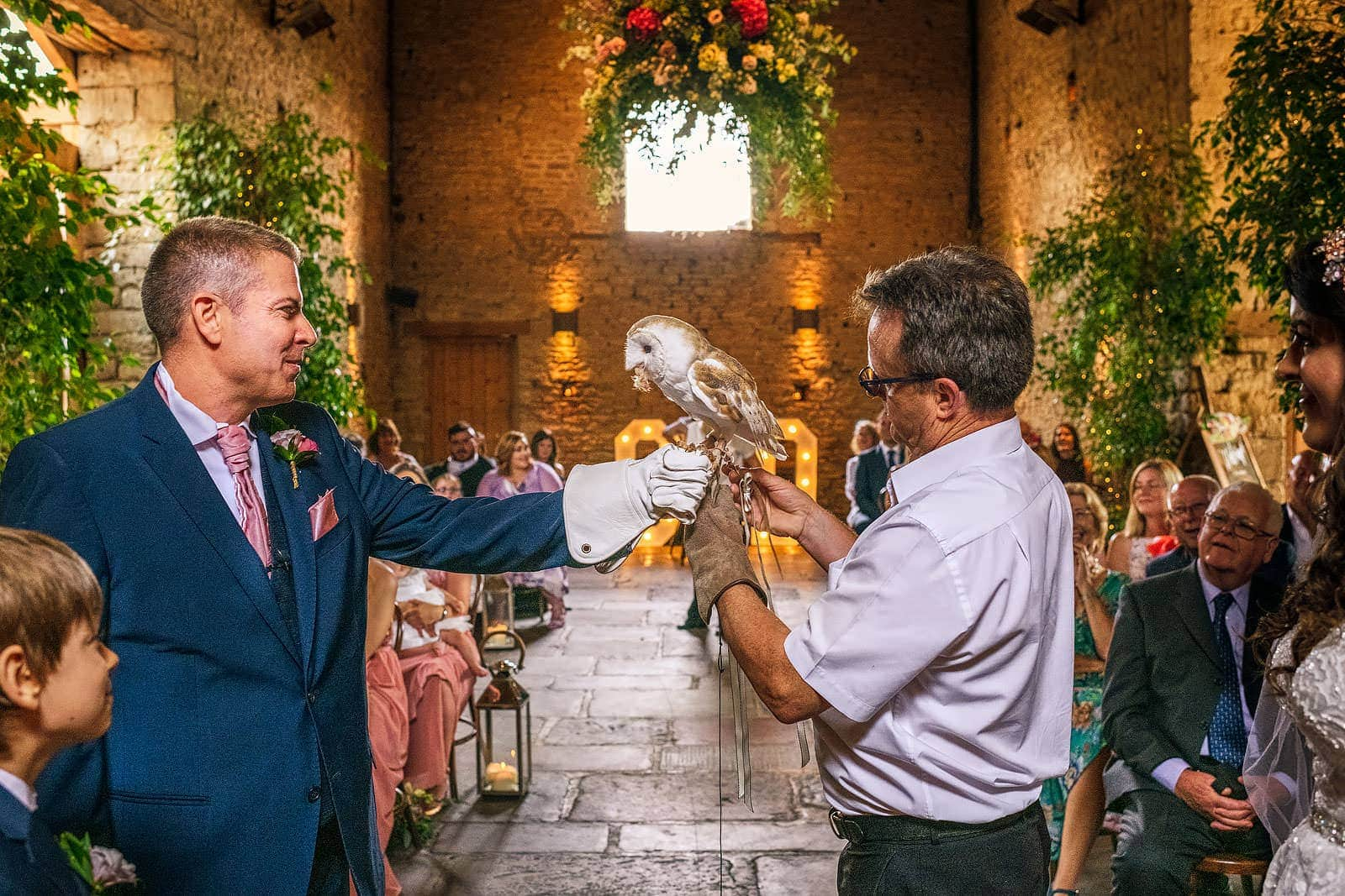 Groom holds an owl during the ceremony