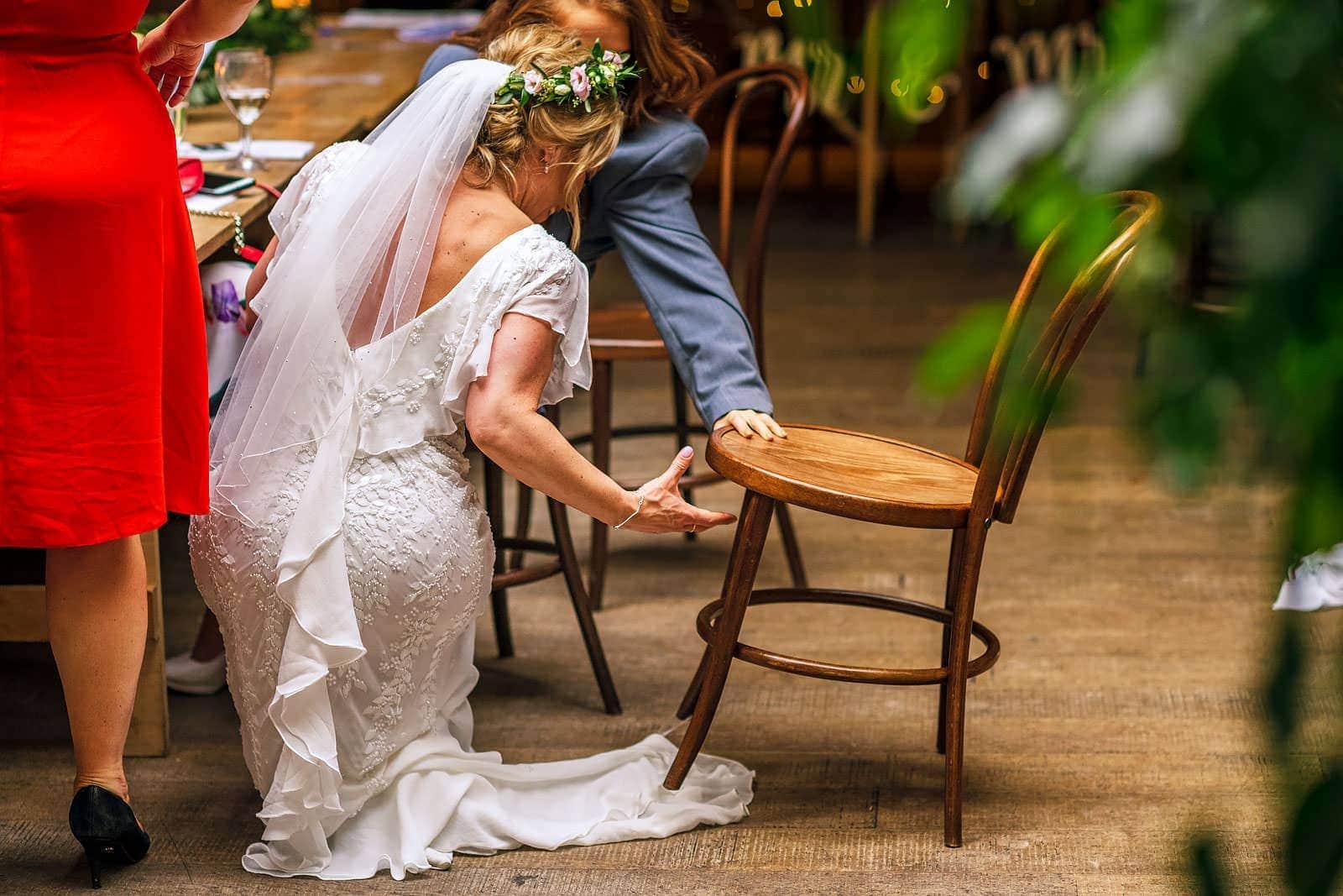 Bride catching dress under chair