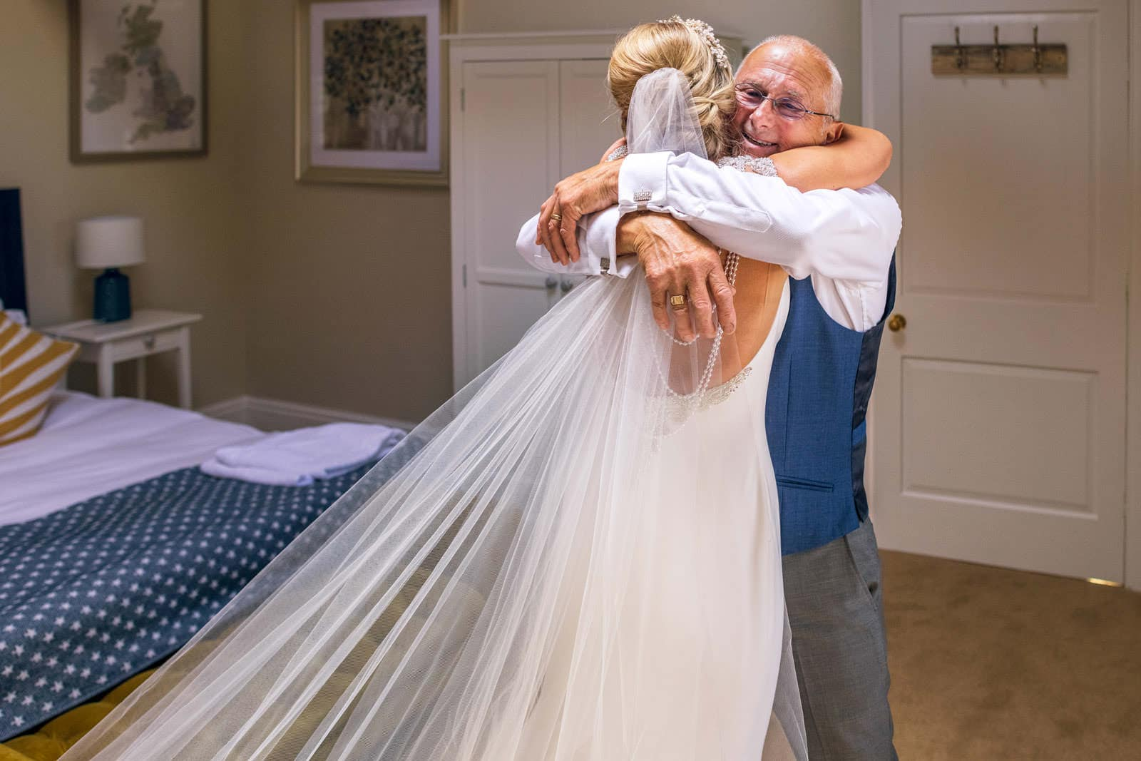 Father of the bride cuddling his daughter