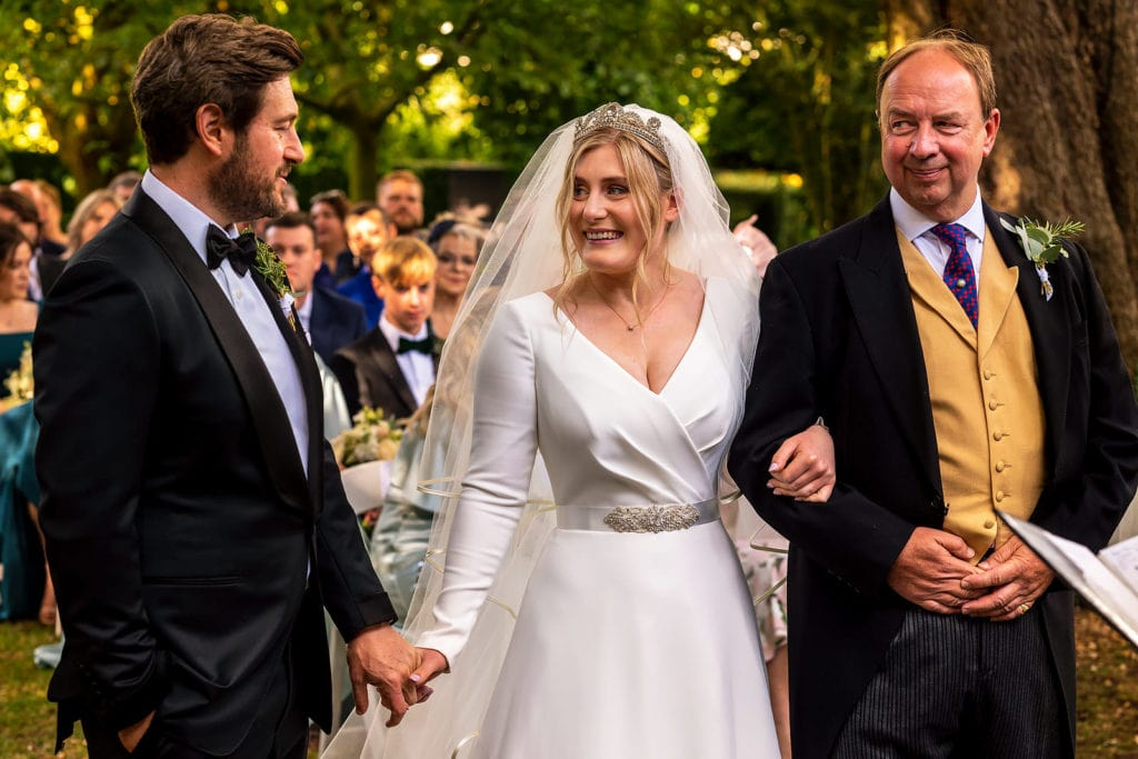 Father of the bride walking his daughter down the aisle at Barnsley House
